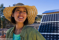 Native American woman standing near solar panels wearing a straw hat. The pretty ethnic woman is looking up with a big smile. She is wearing a floppy straw hat. Behind her are a set of solar panels.